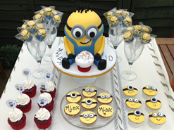 Despicable Me Cake and Cupcakes on a Party Dessert Table
